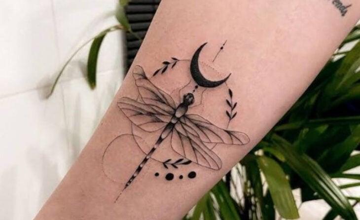 Tatuaje de una libélula en la parte externa del brazo