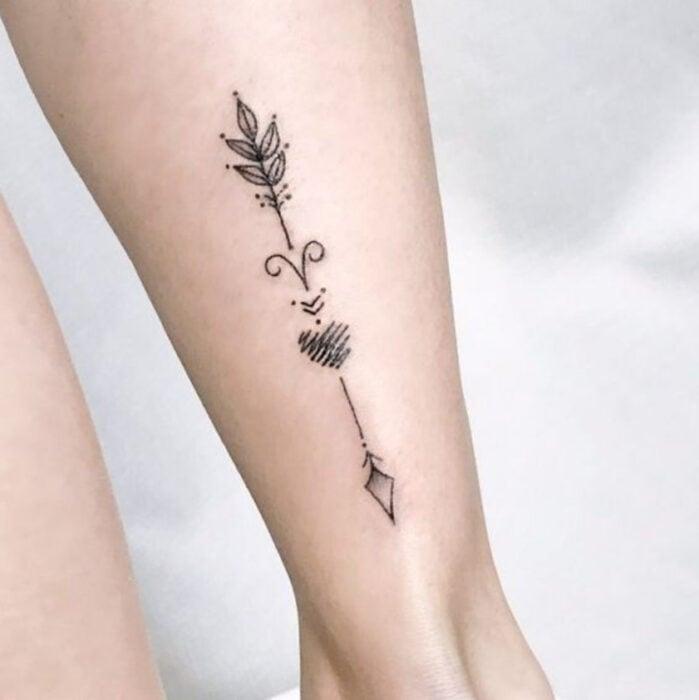 Tatuaje de una flecha en la parte trasera de una pantorrilla