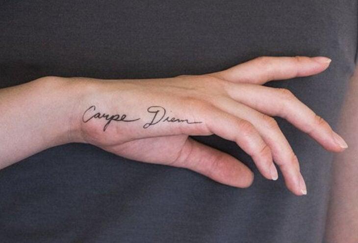 Tatuaje de una frase en la parte lateral de la mano