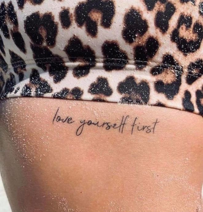 Girl with a tattoo with the phrase love yourself first