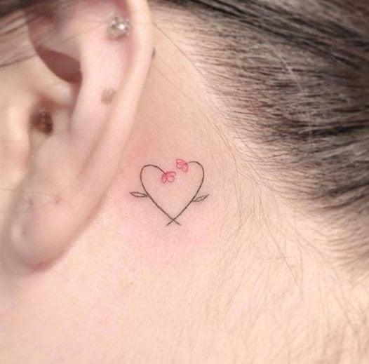 Chica con un tatuaje atrás de la oreja con un corazón y flores