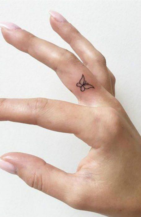 Chica con un tatuaje en forma de mariposa en el dedo medio