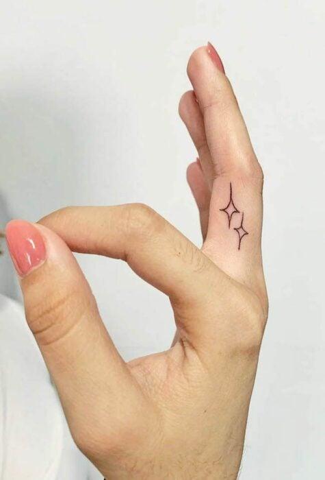 Chica con un tatuaje en forma de estrellas en el dedo medio