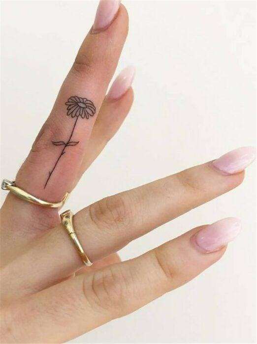 Chica con un tatuaje en forma de flor en el dedo medio