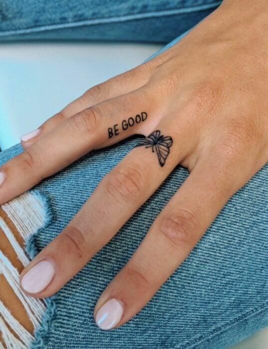 Chica con un tatuaje en forma de mariposa y con letras en el dedo medio y anular