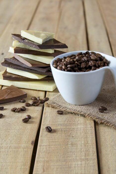 Chocolate en barra junto a una taza de granos de café; Tinte de café y chocolate, el secreto para unas cejas marcadas y gruesas