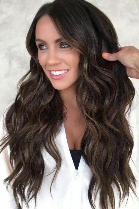 Chica mostrando su cabello en color chocolate con reflejos