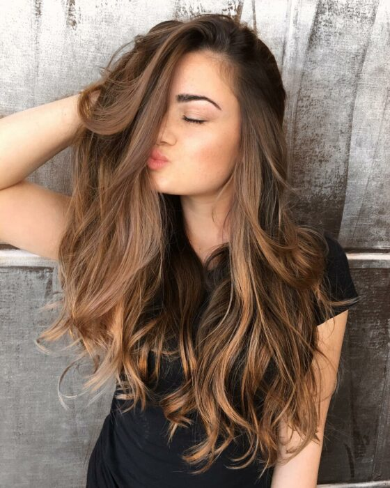 Girl showing her hair dyed in caramel color