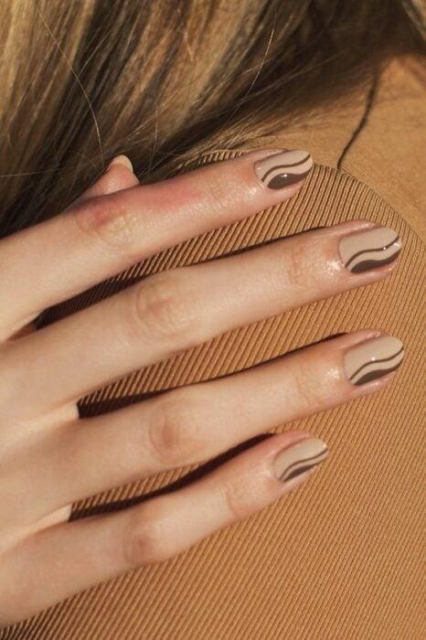 Manicura en tonos café y beige con líneas