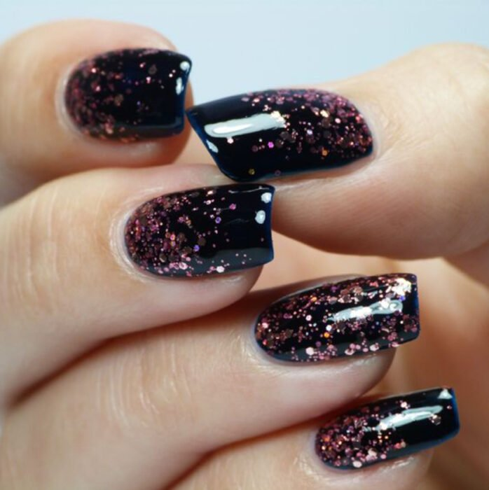 Manicure with black background with sparkles of copper glitter