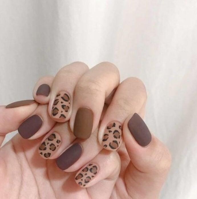 Manicura con diseño en tonos cafés y diseño de animal print