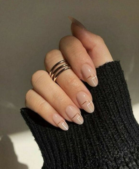Nails with a nude base and brown and white lines