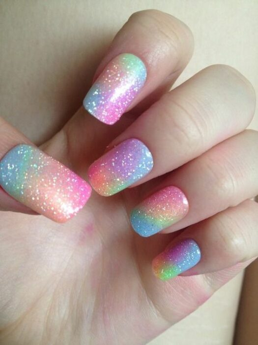 Nails with a rainbow background and silver glitter details