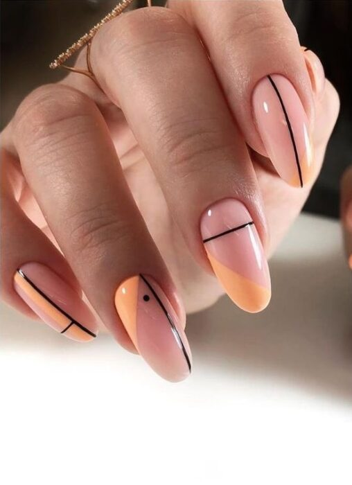 Nails in nude color, with orange and black lines