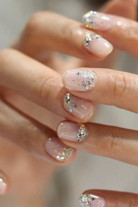 Manicure with a nude background and silver glitter details