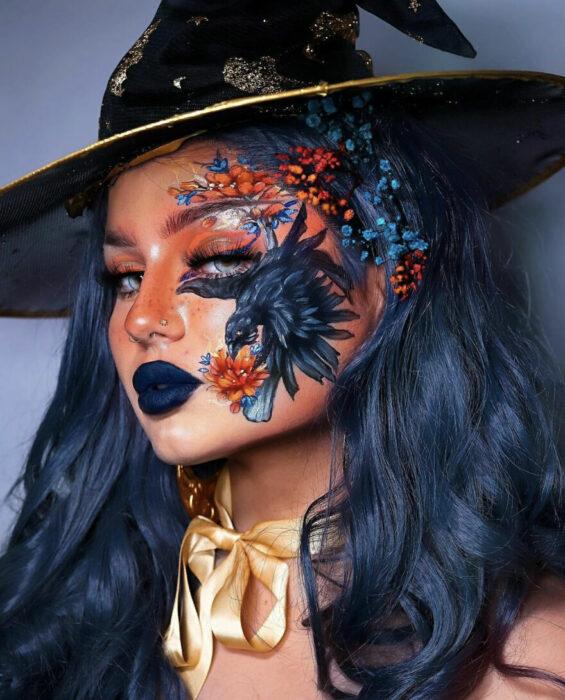 Chica con una ave pintada en el rostro y acompañada de flores negras