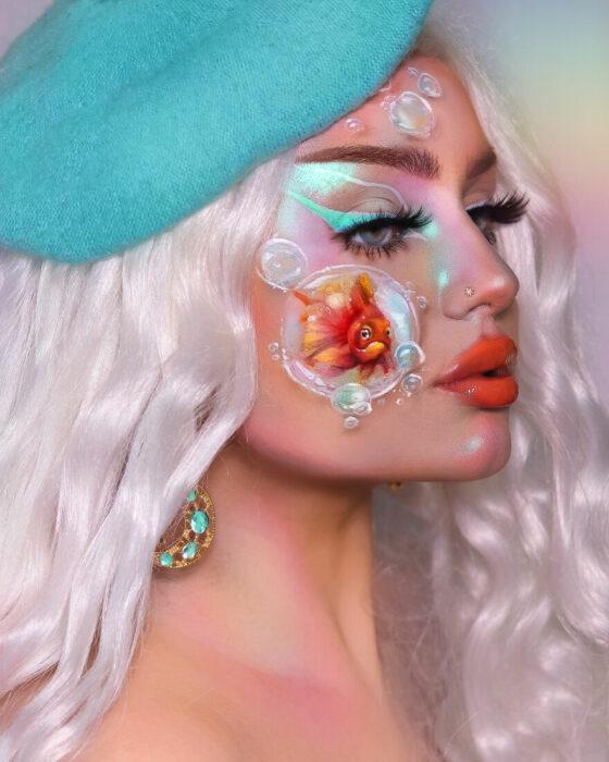 Chica con un pez pintado en uno de sus cachetes