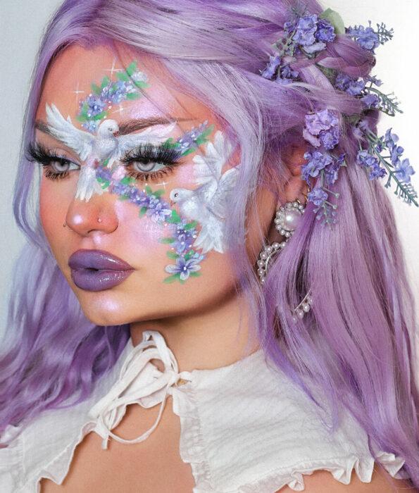 Chica con el rostro pintado con dos palomas blancas y lavanda