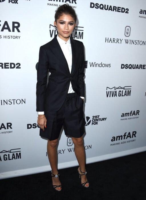 Zendaya wearing a black tomboy style outfit with a white blouse