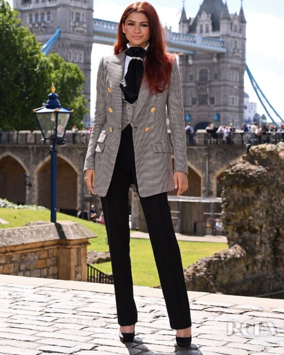 Zendaya wearing a gray tailored suit with black pants and a silk bowtie