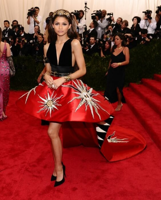 Zendaya wearing a red dress with black and star print during a Met Gala