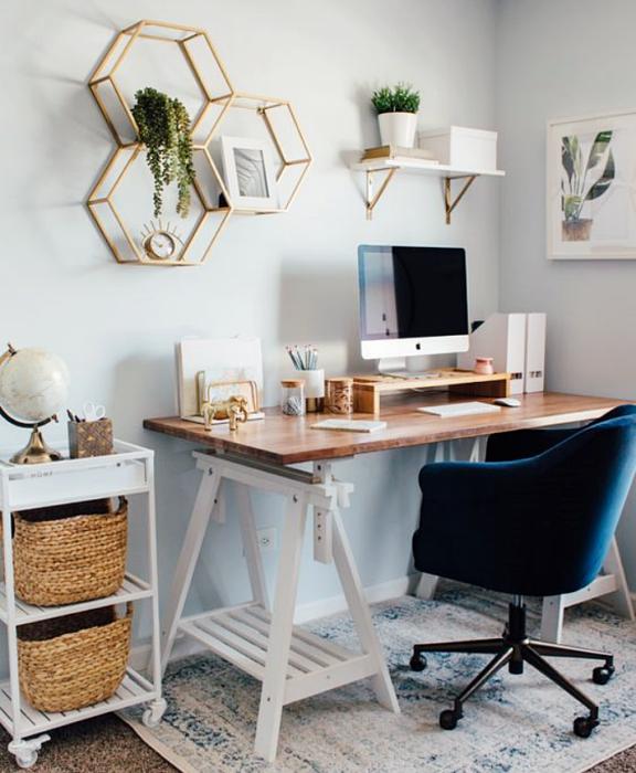 oficina en tonos blancos, grises, minimalista, con escritorio blanco de madera, silla cómoda de oficina, cojines, fotos decorativas, macetas, repisas, alfombra, colores vibrantes, diseño relajado y sencillo