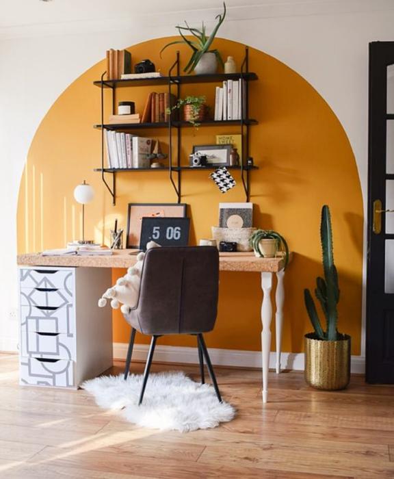 oficina blanca con acento amarillo, repisas delgadas, silla negra, escritorio de madera y plantas