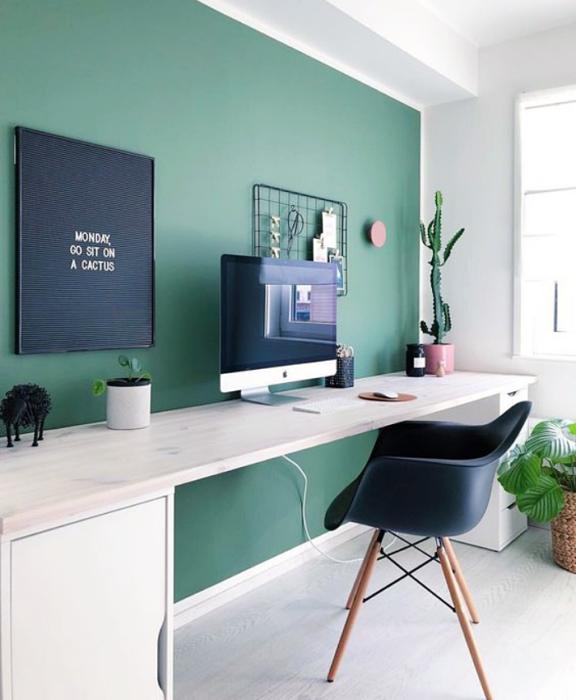 oficina blanca, minimalista con pared verde, silla negra, escritorio blanco y macetas