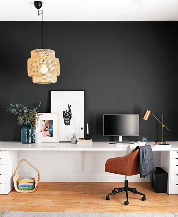 oficina con pared negra, escritorio blanco, silla café moderna y cuadros decorativos blancos, lampara beige