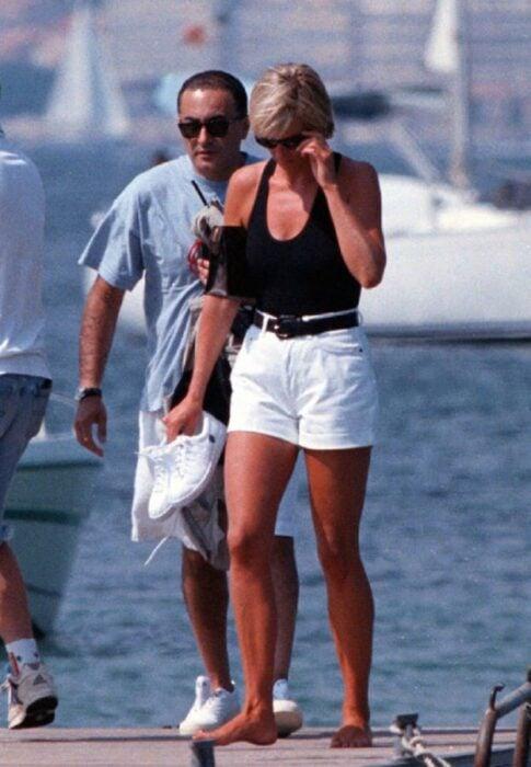 Diana Spencer usando unos shorts de color blanco con una blusa top de color negro mientras camina por un puerto