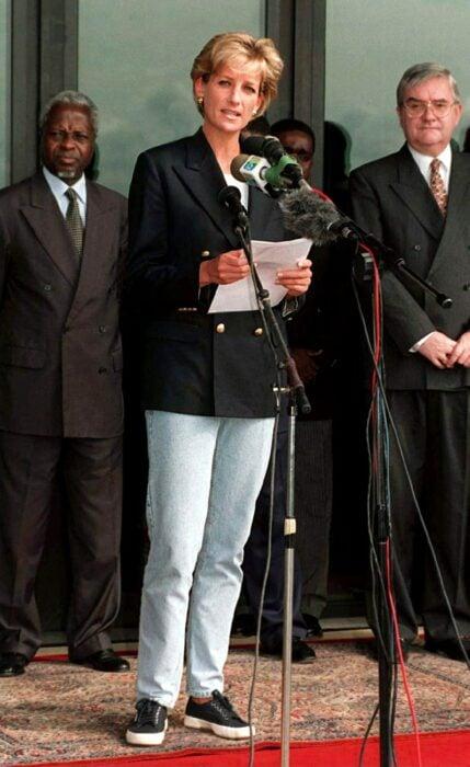 Diana Spencer dando un discurso en Angola mientras usa jeans, tenis y una chaqueta