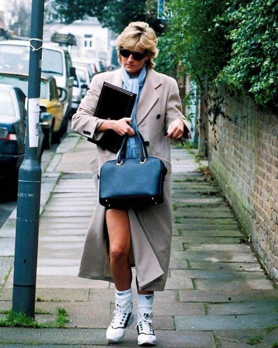 Diana de gales usando un abrigo largo y tenis mientras va caminando por la calle