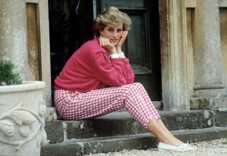 Diana Spencer sentada en las escaleras del palacio usando un outfit de color rosa