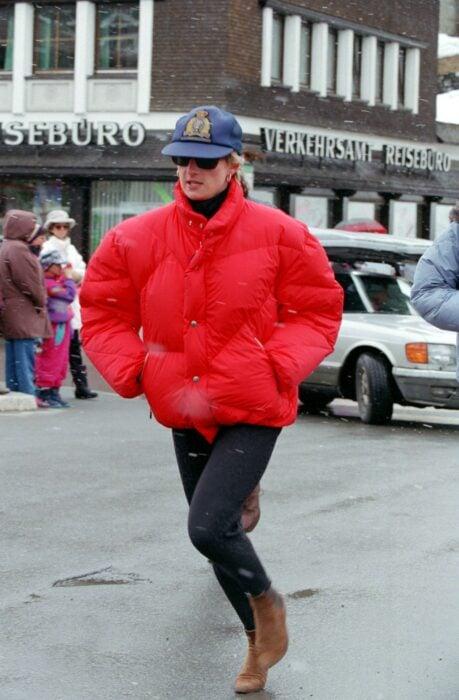 Diana spencer usando una puffer Jacket en color roja con una gorra