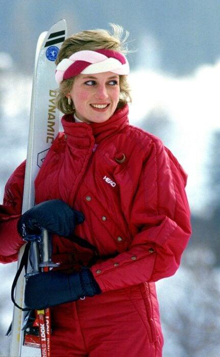 Lady Di usando un traje para esquiar en color rojo  con guantes negros