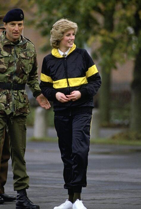 Diana Spencer usando un conjunto deportivo en color negro con amarillo