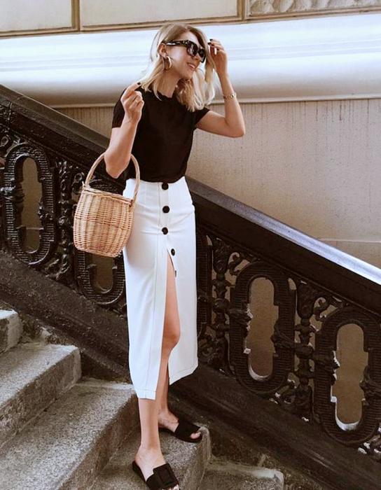 chica rubia usando un top negro de manga corta, falda larga blanca abierta con botones negros, flats negros