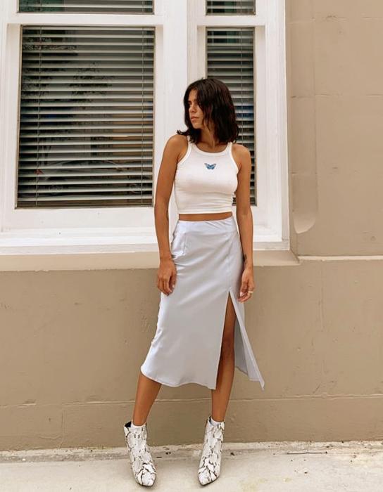 chica morena con crop top blanco de tirantes, falda larga abierta de satén celeste y botines plateados de tacón