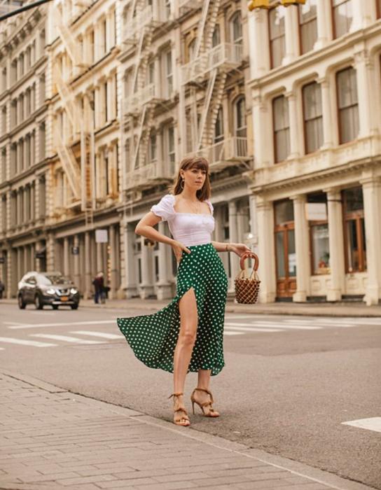 chica de cabello castaño usando una blusa blanca de manga corta, falda larga verde abierta con lunares blancos y sandalias de tacón café claro