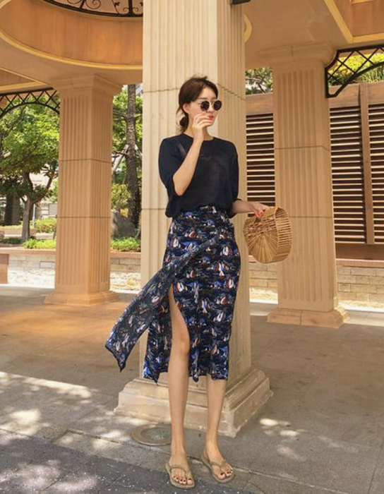 chica de cabello castaño usando lentes de sol, blusa azul marino, falda azul con flores larga abierta. sandalias de piso color café claro