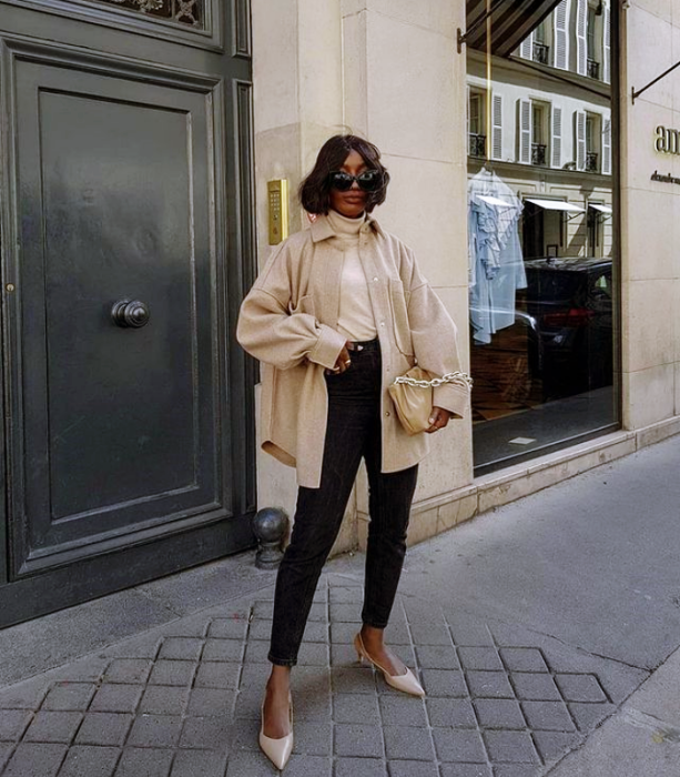 brunette girl with short dark hair wearing sunglasses, tight black jeans, beige flats, beige top and beige coat