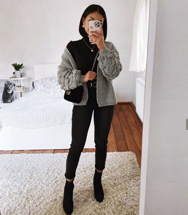 black short hair girl wearing black high neck top, gray knitted cardigan, black skinny jeans, black leather ankle boots