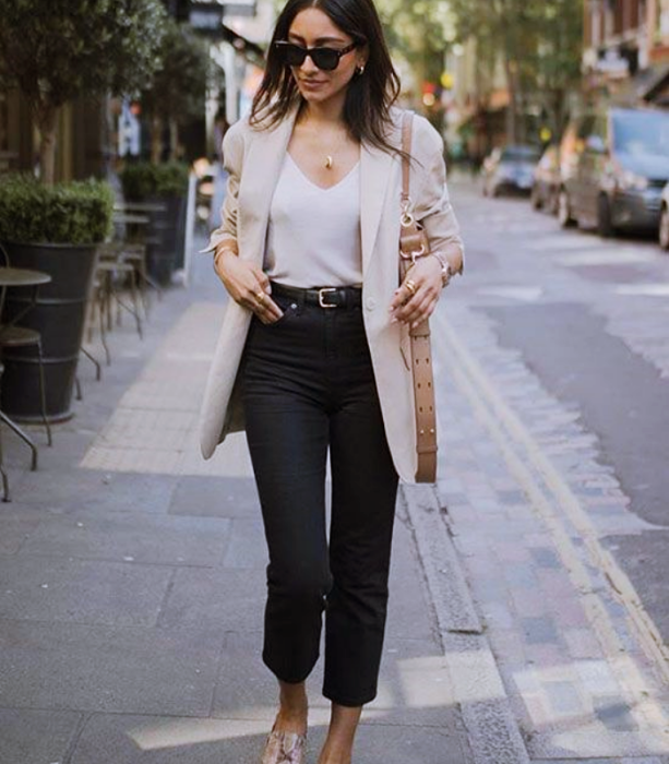 girl with long dark hair, sunglasses, white top, beige blazer, black jeans, snake animal print flats