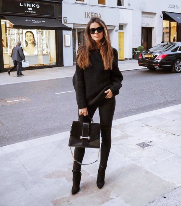 long light hair girl wearing sunglasses, black sweater, black skinny jeans, black high heel ankle boots