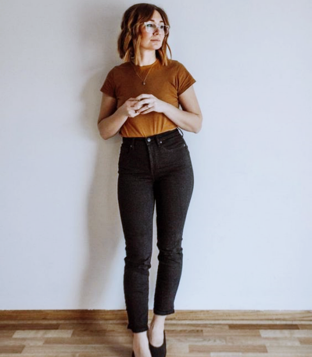 chica de cabello claro usando una camiseta café, jeans negros ajustados y flats negros