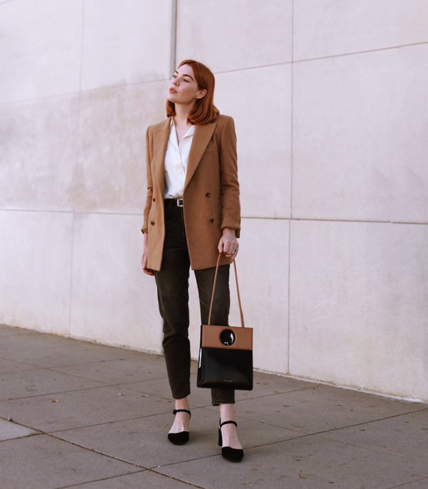 redhead girl with short hair, white top, black jeans, black high heels, brown bag with black