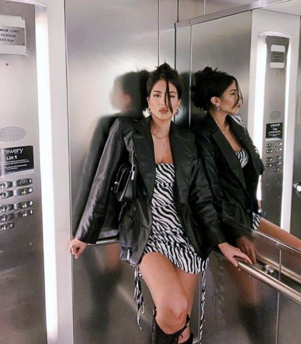 chica de cabello oscuro usando un vestido de cebra corto, chaqueta de cuero, botas de cuero largas y bolso negro