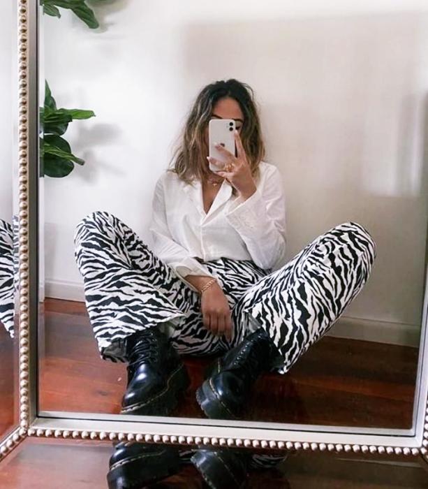 chica de cabello claro usando una blusa blanca, pantalones de cebra acampanados, botines negros de cuero