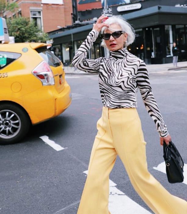 mujer mayor usando lentes de sol, cabello blanco, blusa de cebra de manga larga, pantalones amarillos acampanados y bolso negro de cuero