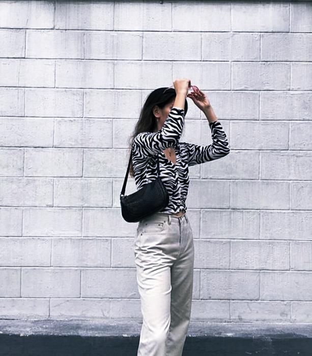 chica de cabello oscuro, bolso negro pequeño, pantalones blancos, blusa de cebra de manga larga con escote de nudo